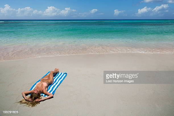 Woman laying on towel on beach