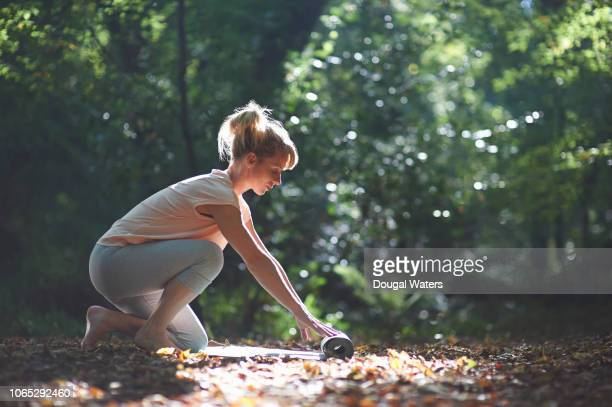 Woman laying out yoga mat in autumn woodland.