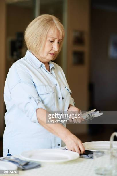 woman laying table for guests - cliqueimages stockfoto's en -beelden