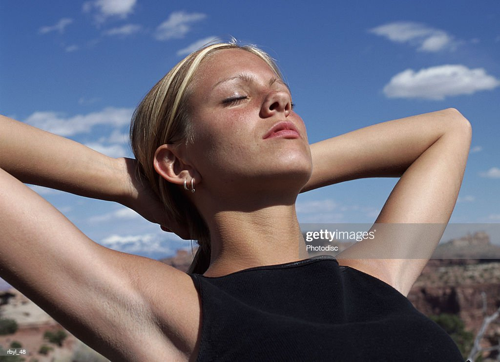Woman laying with eyes closed and hands behind head, high section : Foto de stock