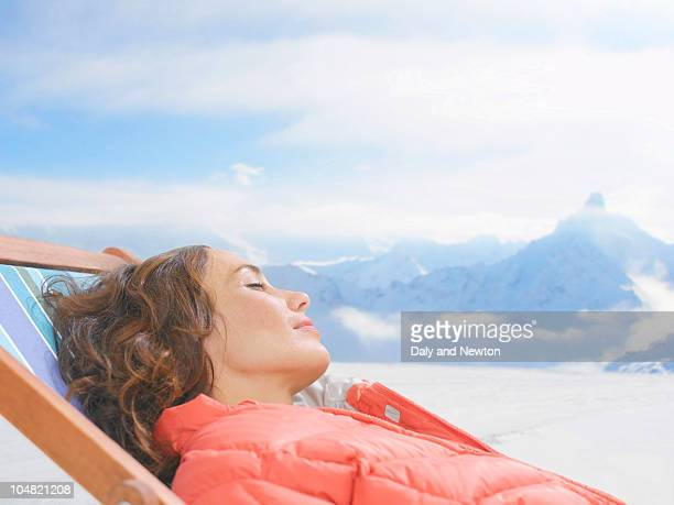 Woman laying with eyes closed on lounge chair on snowy mountain