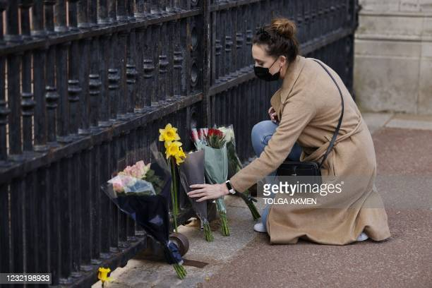 Woman lays a bunch of flowers at the gates of Buckingham Palace in central London on April 9, 2021 after the announcement of the death of Britain's...