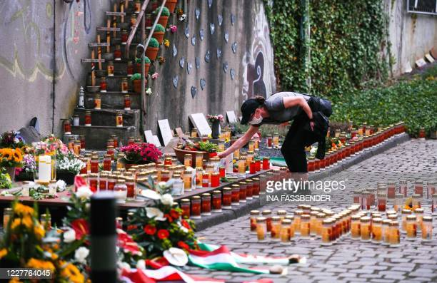 Woman lays a candle during a commemoration at the Love Parade Memorial on July 24, 2020 in Duisburg, western Germany, on the day marking 10 years...