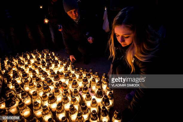 A woman lays a candle in front of the government office during a silent protest march in memory of Murdered Slovak journalist Jan Kuciak and his...