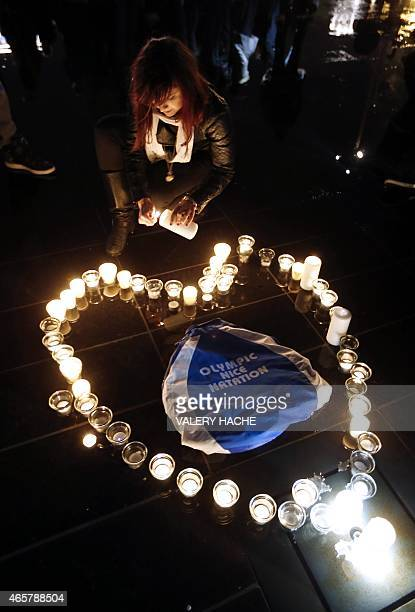 A woman lays a candles to form a heart around a bag reading Nice Olympic Swimming during a candlelight vigil for swimming gold medallist Camille...