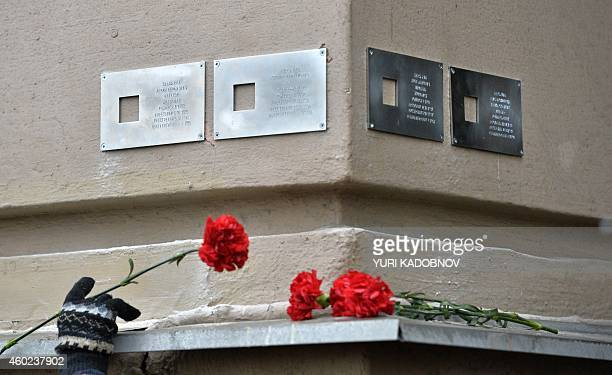 A woman lays a flower next to commemorative plaques to the victims of Soviet repression installed on the wall of their former house in central Moscow...
