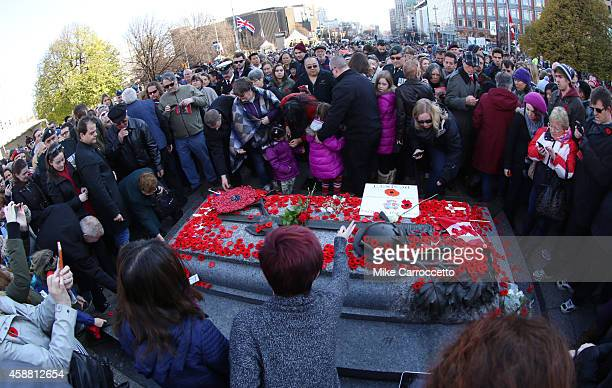 A woman lays a poppy on the Tomb of the Unknown Soldier after this morning's Remembrance Day ceremony November 11 2014 in Ottawa Canada An estimated...