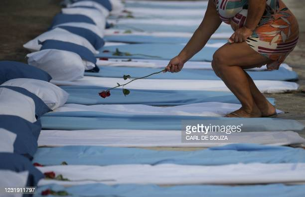 Woman lays a rose on top of a mattress symbolizing COVID-19 victims during a protest by the Rio de Paz human rights activist group outside a hospital...