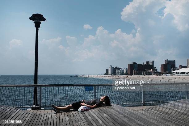 A woman lays along the boardwalk at Coney Island on a hot summer afternoon on August 7 2018 in New York City New York City is enduring another day of...