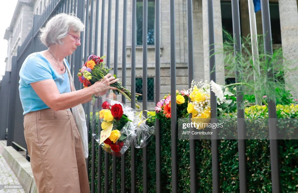 A woman lays down flowers at the fence of the Spanish embassy in Berlin, on August 18, 2017 in tribute to victims of the Barcelona attack. A driver rammed a van into a crowd on Barcelona's famous avenue Las Ramblas on August 17, 2017 afternoon, while eight hours later, an Audi A3 car ploughed into pedestrians in the seaside city of Cambrils. / AFP PHOTO / Odd ANDERSEN