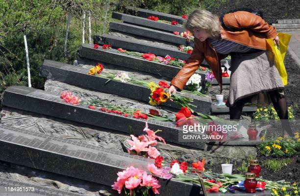 Woman lays flowers at a Chernobyl memorial in Kiev during the 22nd anniversary commemoration ceremony on April 26, 2008. On 26 April 1986, the No 4...