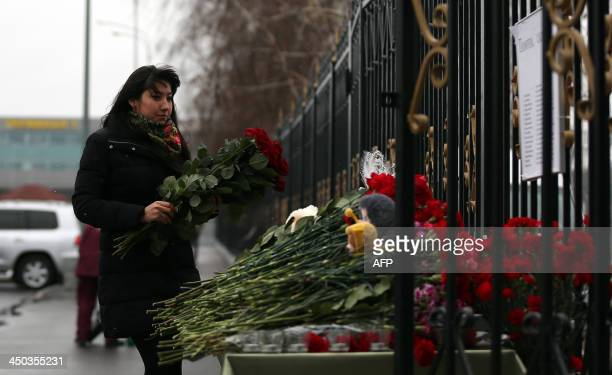 A woman lays flowers at a list of the recent plane crash victims in the international airport of Russia's Volga city of Kazan on November 18 2013 A...