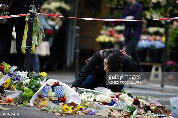 A woman lays flowers at a makeshift memorial outside the cafe 'A la Bonne Biere'' on November 17 2015 in tribute to the victims of the Paris attacks...