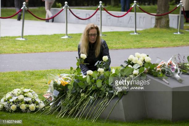 Woman lays flowers at a monument pictured ten years after a man rammed his car into bystanders in an attack on the Dutch royal family on...