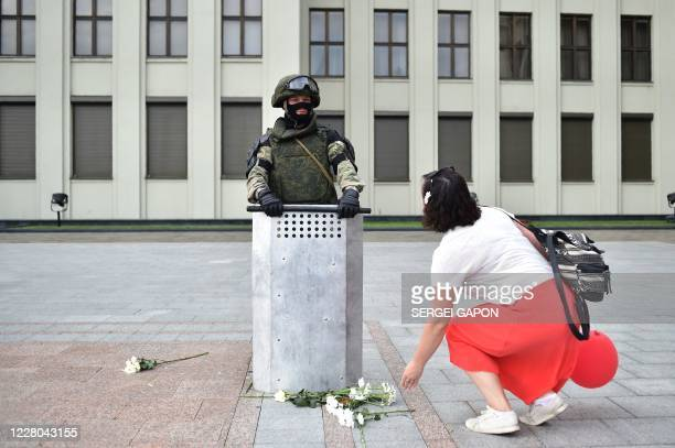 TOPSHOT A woman lays flowers at the feet of a Belarus' law enforcement officer as he guards a Government building during a protest rally against...
