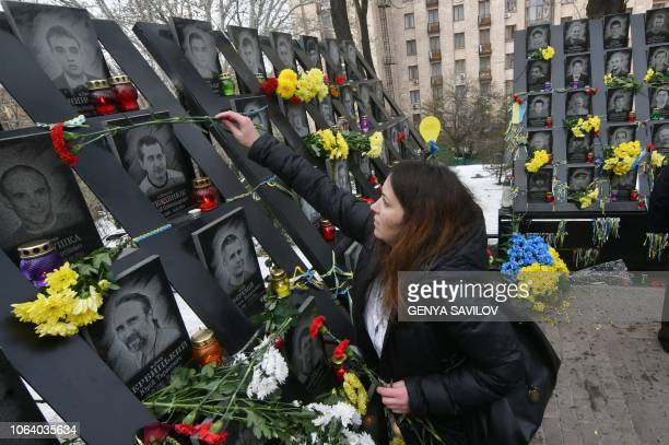 A woman lays flowers at the memorial for the killed Maidan activists during a ceremony marking the fifth anniversary of the Euromaidan beginning in...