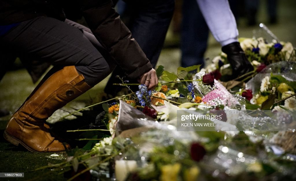 A woman lays flowers at the memorial site for the late linesman Richard Nieuwenhuizen at the SC Buitenboys clubhouse in Almere, on December 9, 2012. Nieuwenhuizen collapsed and fell into a coma after he was attacked by three teenagers at the end of a junior club football match on December 2, 2012. People gathered this afternoon for a silent march in memory of Nieuwenhuizen. AFP PHOTO / ANP / KOEN VAN WEEL netherlands out