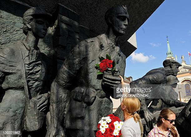 A woman lays flowers at the monument dedicated to heroes of the Warsaw Uprising in Warsaw's Old Town on August 1 to mark the 67th anniversary of the...