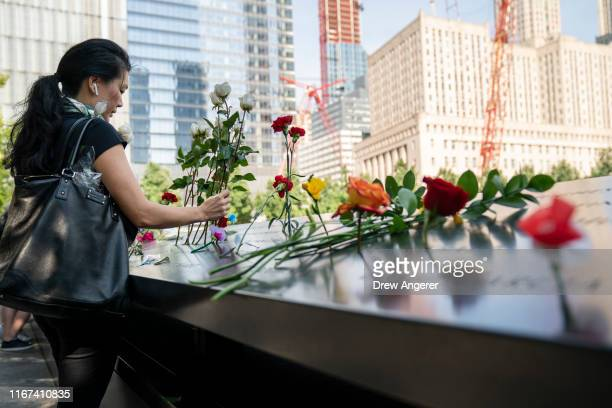 A woman lays flowers at the National September 11 Memorial on the 18th anniversary of the 9/11 attacks September 11 2019 in New York City Throughout...