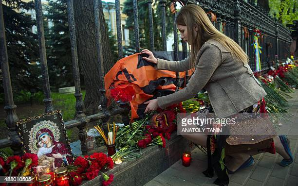 Woman lays flowers by the fence of the Ukrainian embassy in Moscow on May 3 in honour of people killed during clashes in Odessa. Ukrainian soldiers...