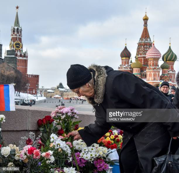 A woman lays flowers in central Moscow on February 25 2018 at the site where late opposition leader Boris Nemtsov was fatally shot on a bridge near...