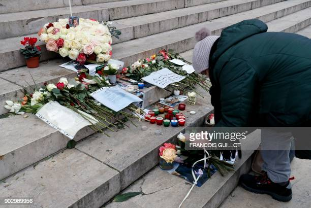 A woman lays flowers in tribute to late French musician Johnny Hallyday on the stairs in front of the La Madeleine Church in Paris on January 9 2018...