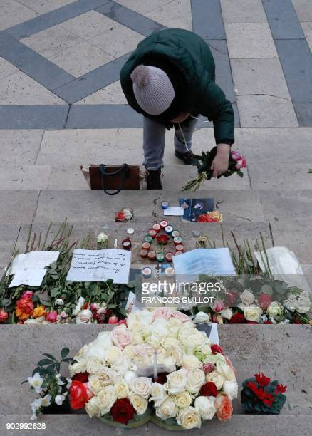 A woman lays flowers in tribute to the late French musician Johnny Hallyday at La Madeleine Church in Paris on January 9 2018 French music icon...