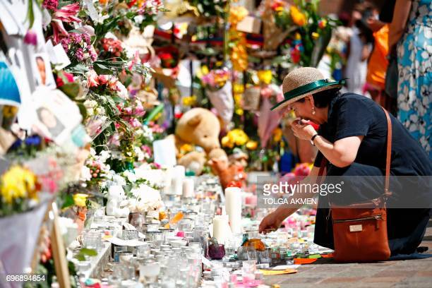 TOPSHOT A woman lays flowers in tribute to the victims of the June 14 Grenfell Tower block fire in Kensington west London on June 17 2017 Angry...