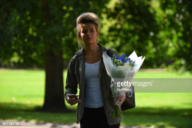 A woman lays flowers near the Golden Gates of Kensington Palace ahead of the 20th anniversary of Princess Diana's death London on August 31 2017...
