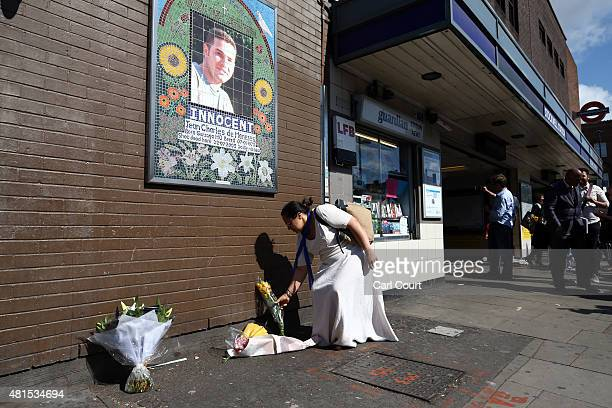 A woman lays flowers under a mosaic of Brazilian national Jean Charles de Menezes during a memorial to mark the 10th anniversary of his death on July...
