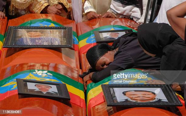 A woman lays on the coffin of her loved one during a memorial service for the Ethiopian passengers and crew who perished in the Ethiopian Airways...