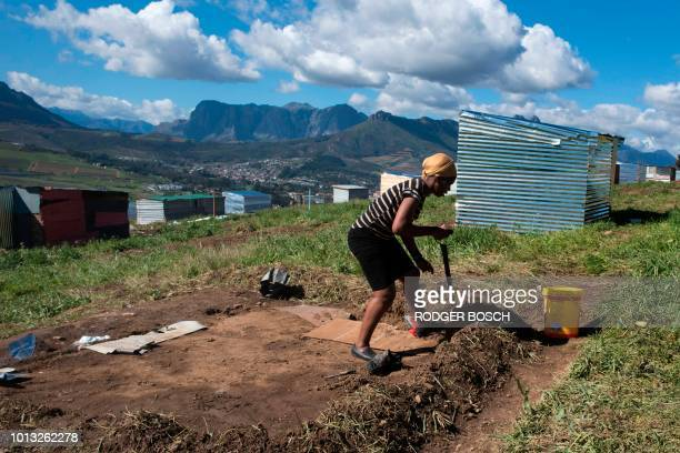 A woman lays out plot on a piece of land belonging to the Louiesenhof Wine Estate on August 8 in Stellenbosch which is at the centre of the South...