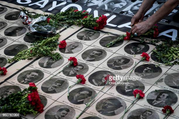 A woman lays roses over the portraits of victims during a memorial to commemorate the 1915 Armenian mass killings on April 24 2018 in Istanbul Turkey...