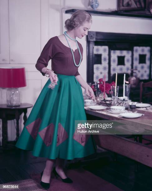 A woman lays the table in preparation for guests circa 1955