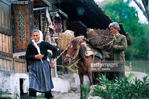 Woman leading a horse in front of the old bazaar in Kruje, Albania.