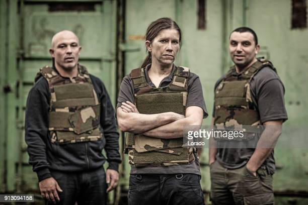 woman leading a krav maga fighting group posing for team picture in grimy outdoor setting - army training stock pictures, royalty-free photos & images