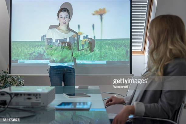 Woman leading a presentation with projector in conference room