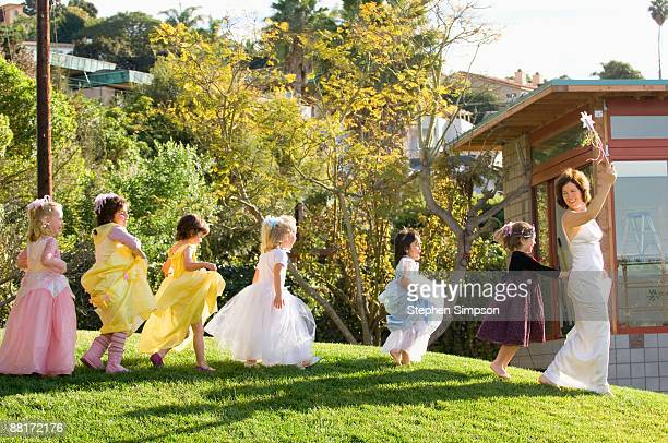 woman leading dressed up girls in line through yard - princess stock pictures, royalty-free photos & images