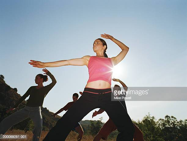 Woman leading group of people in tai-chi position, low angle