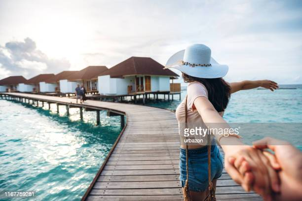 woman leading man to exploring - following stock pictures, royalty-free photos & images
