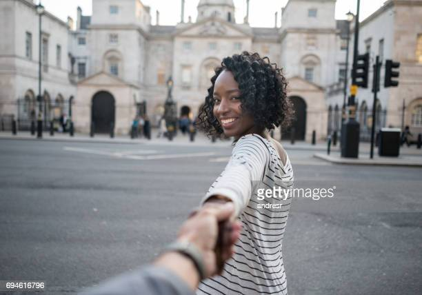 woman leading the way while traveling in london - following stock pictures, royalty-free photos & images