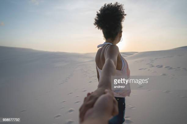 woman leading the way while traveling in the desert - following stock pictures, royalty-free photos & images