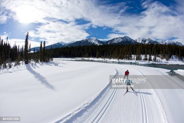 a woman leads a man on a cross-country skate ski in british columbia, canada. - canadian rockies stock pictures, royalty-free photos & images