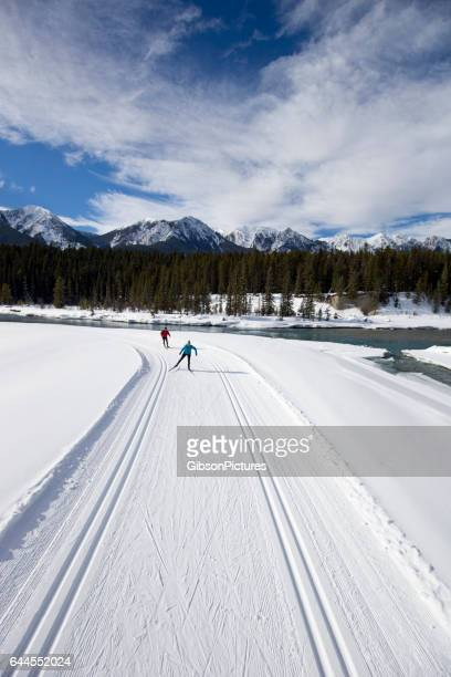 A woman leads a man on a cross-country skate ski next to a river in British Columbia, Canada.