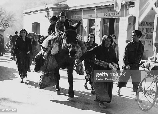 A woman leads a mule laden with belongings through the streets of Perthus during the Spanish Civil War Spain 1939 | Location Perthus Spain