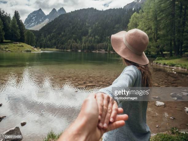 de vrouw leidt vriend op alpien meer in de zomer - volgen activiteit stockfoto's en -beelden