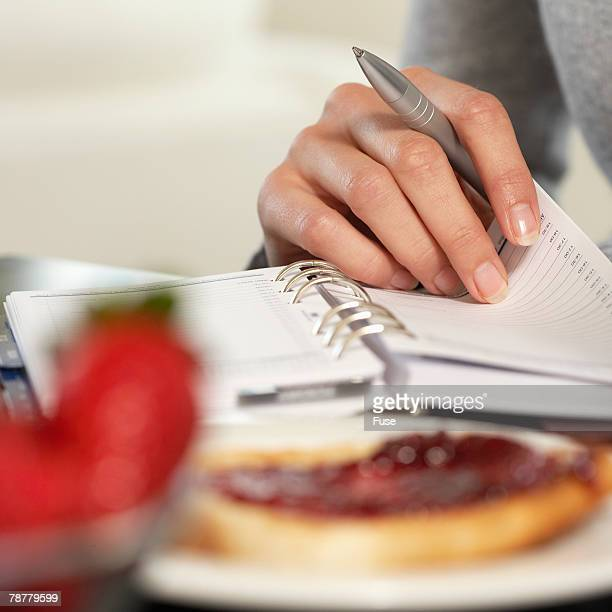 woman leafing through datebook - time management stock photos and pictures