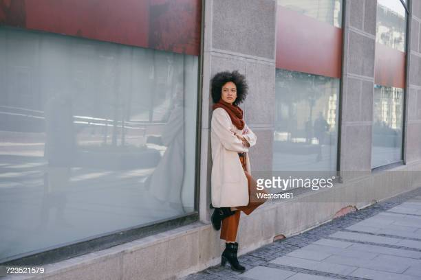 Woman leaning against a building looking sideways
