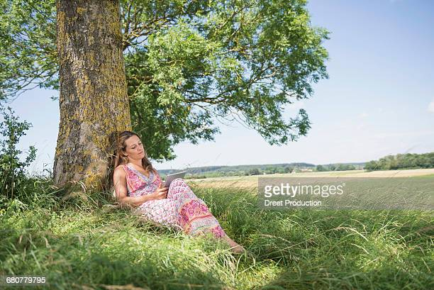 Woman leaning against a tree and using digital table on picnic, Bavaria, Germany