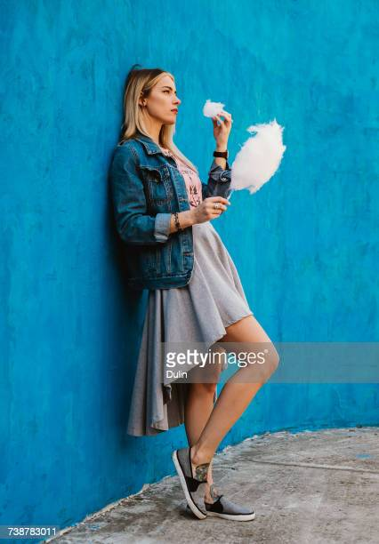 Woman leaning against a wall eating cotton candy